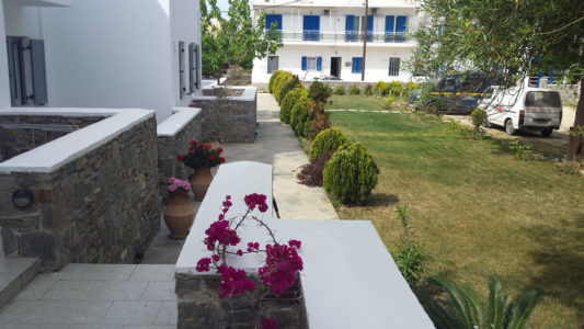 Outside view of Hotel Indigo Studios in Santorini: Flowers, bushes and the garden